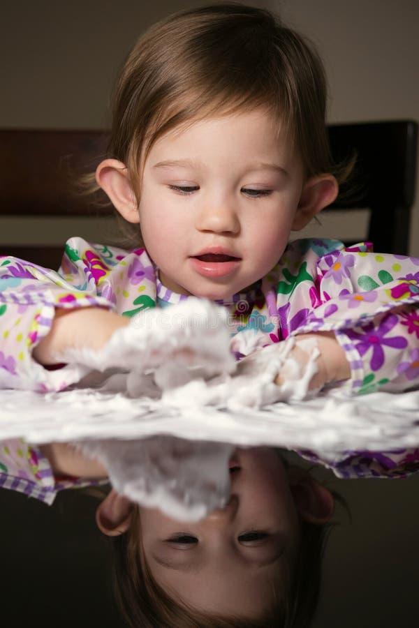 Enfant en bas âge créatif jouant avec la mousse blanche image stock