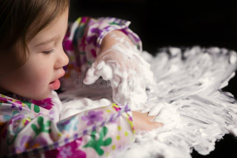 Enfant en bas âge créatif jouant avec la mousse blanche photographie stock libre de droits