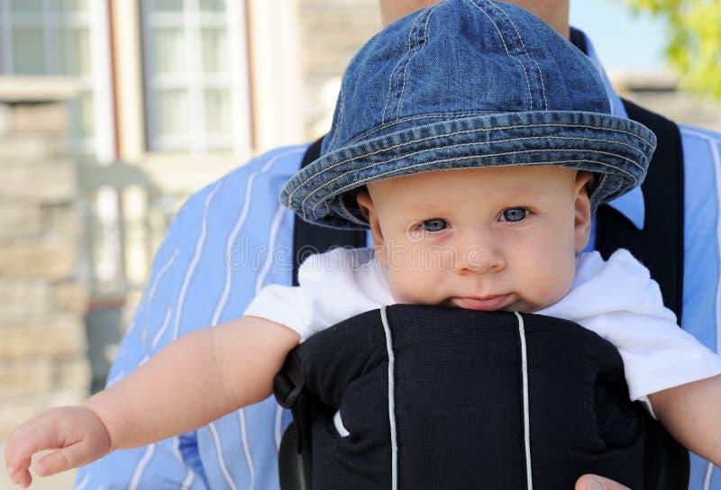Enfant en bas âge de œil bleu dans un transporteur de chéri image libre de droits
