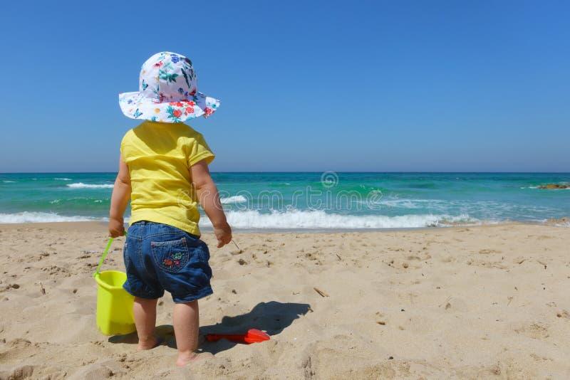 Enfant en bas âge de bébé avec le seau et la pelle sur la plage photo stock