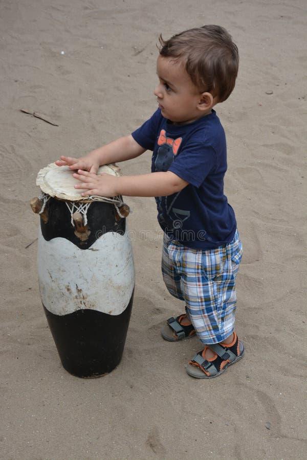 Enfant en bas âge européen jouant avec le tambour africain images libres de droits