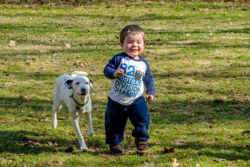 Enfant en bas âge heureux avec le crabot images stock
