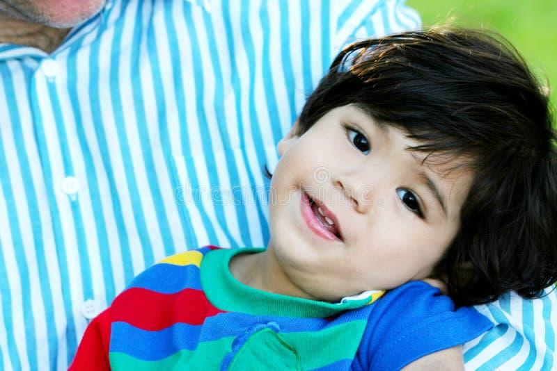 Enfant en bas âge heureux dans le père ; bras de s image libre de droits