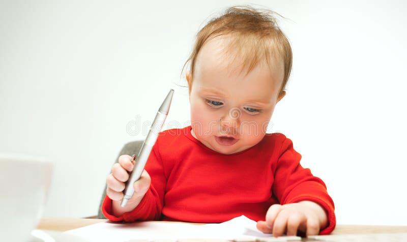 Enfant en bas âge heureux de bébé d'enfant s'asseyant avec le clavier de l'ordinateur d'isolement sur un fond blanc photographie stock libre de droits