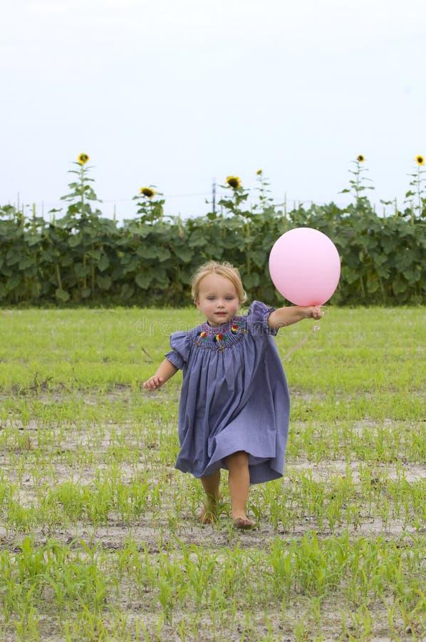 Enfant en bas âge heureux exécutant avec le ballon photo stock