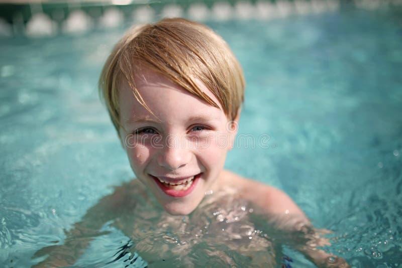 Enfant en bas âge heureux riant dans la piscine photo stock