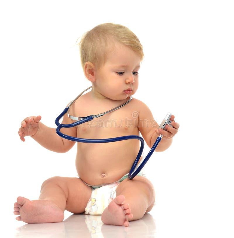 Enfant en bas âge infantile de bébé d'enfant s'asseyant avec le stéthoscope médical pour p photographie stock libre de droits