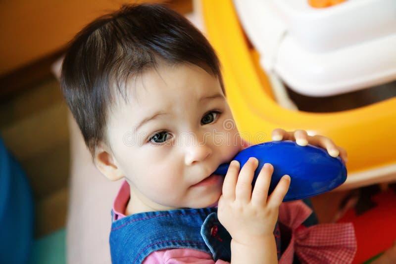 Enfant en bas âge infantile mignon de bébé d'enfant reposant et mangeant le jouet bleu photos libres de droits