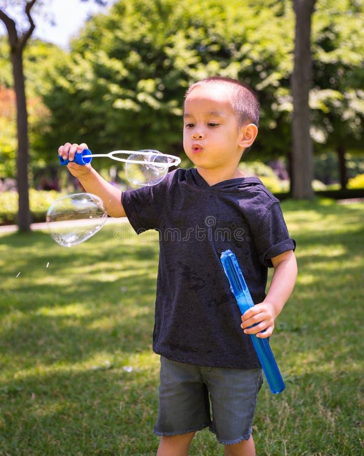 Enfant en bas âge jouant avec des bulles image libre de droits