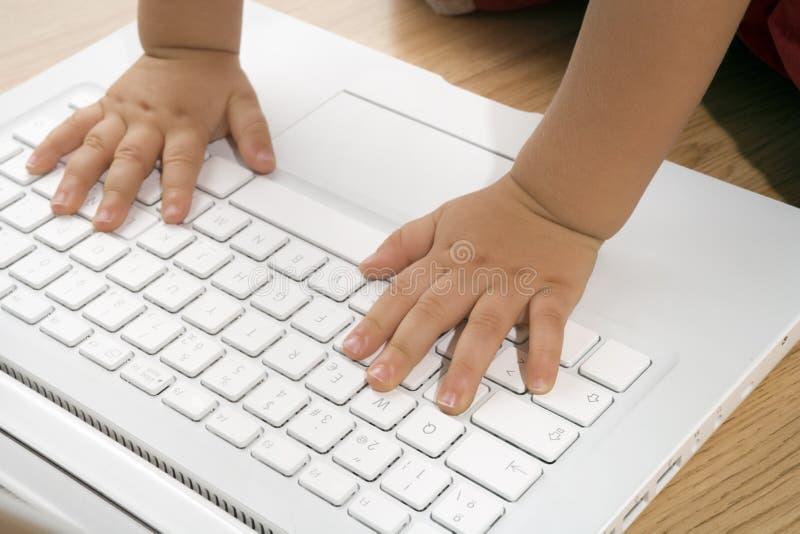 Enfant en bas âge jouant avec l'ordinateur portatif image libre de droits