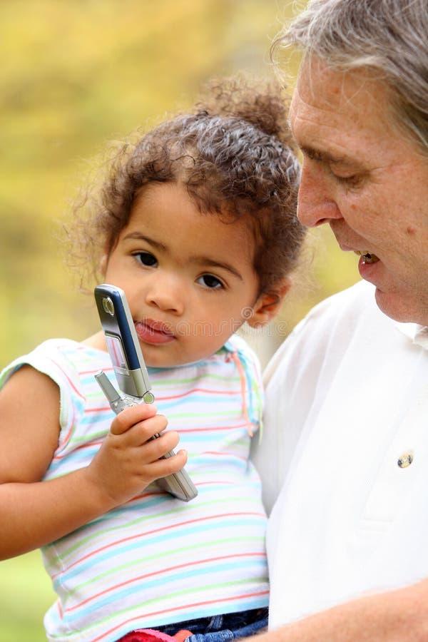Enfant en bas âge jouant avec le portable image stock