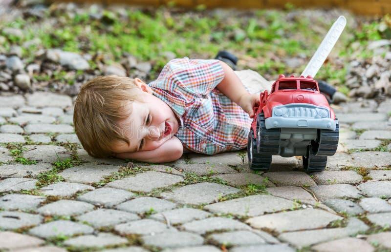 Enfant en bas âge jouant avec Toy Fire Truck Outside - série 6 photo libre de droits