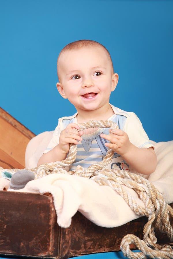 Enfant en bas âge jouant avec une corde se reposant sur un fond bleu photos stock