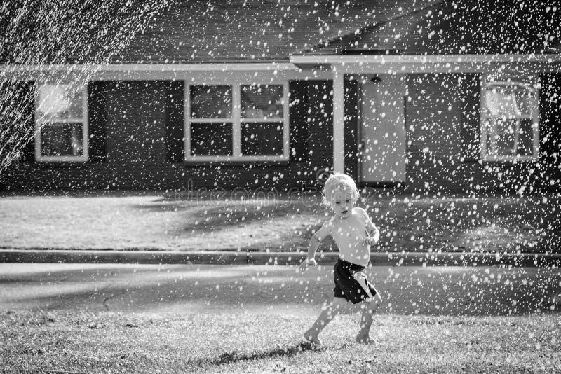 Enfant en bas âge jouant dehors dans la cour images stock
