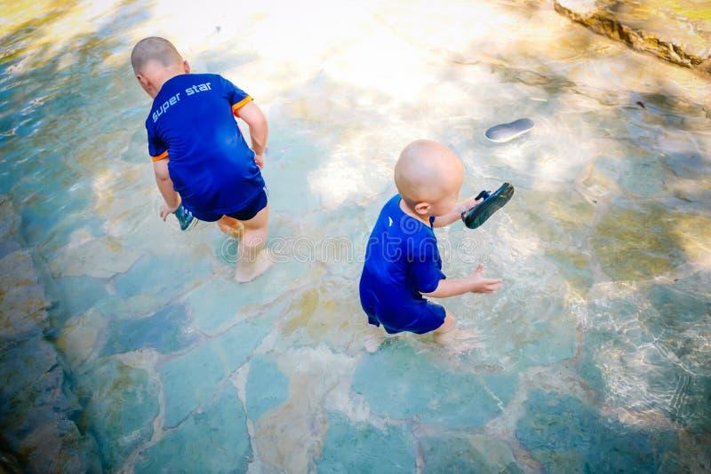 Enfant en bas âge jouant dehors dans le courant photo libre de droits