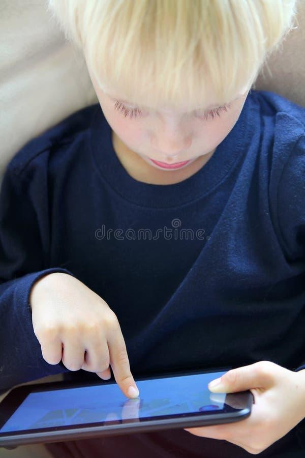 Enfant en bas âge jouant le jeu d'Internet sur la Tablette d'ordinateur photographie stock libre de droits