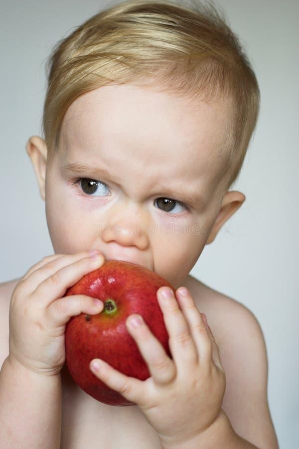 Enfant en bas âge mangeant Apple photographie stock