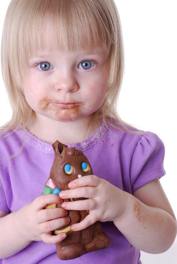 Enfant en bas âge mangeant le lapin de chocolat images stock