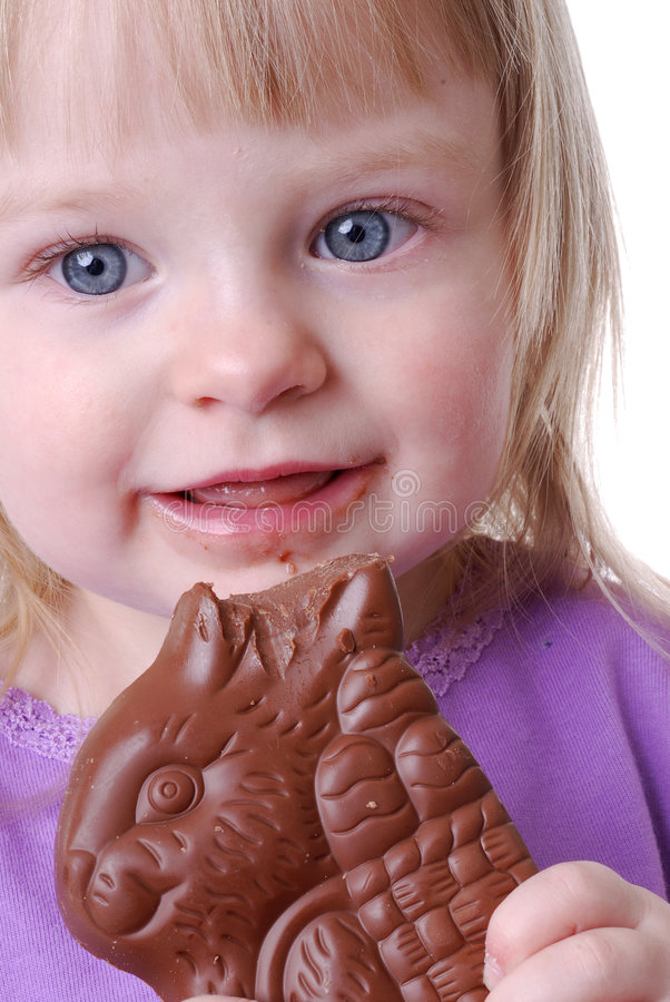 Enfant en bas âge mangeant le lapin de chocolat photos libres de droits