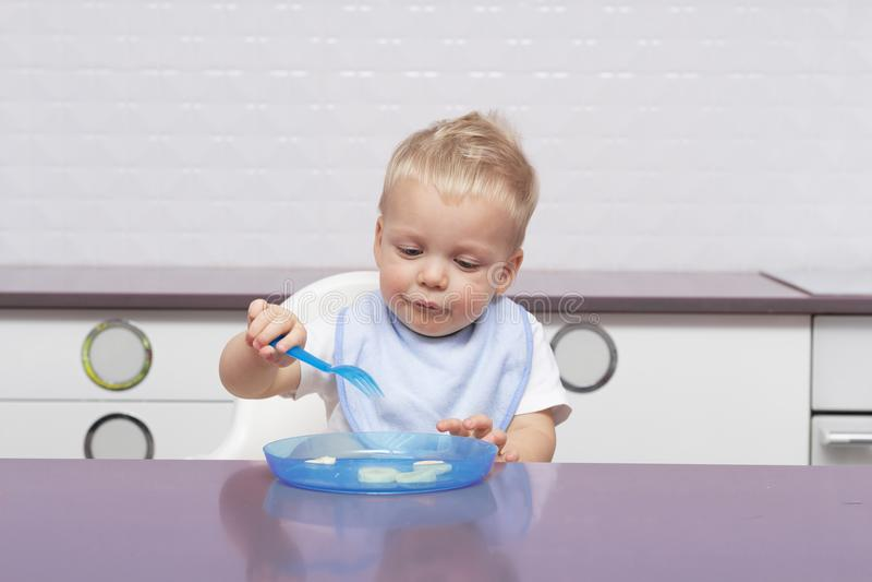 Enfant en bas âge mignon dans un bavoir bleu mangeant la banane dans la cuisine moderne photo stock