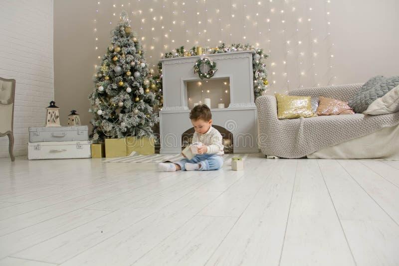 Enfant en bas âge mignon jouant avec son cadeau de Noël dans la salle décorée Jouet en bois Matin de Noël de famille dans décoré image libre de droits