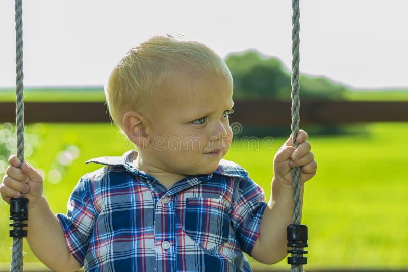 Enfant en bas âge mignon sur une oscillation dehors Portrait de bébé garçon adorable jouant sur un terrain de jeu d'enfant images stock