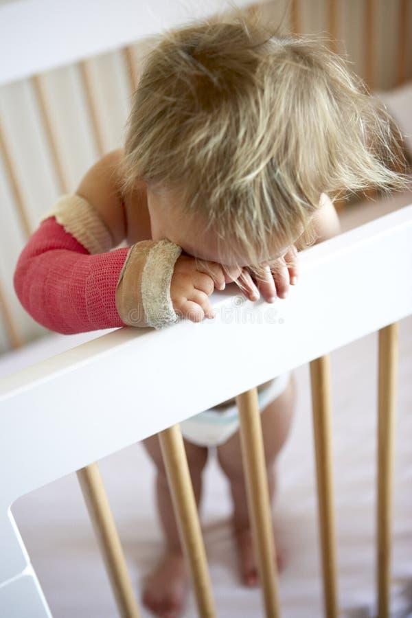 Enfant en bas âge pleurant avec le bras dans le moulage image stock
