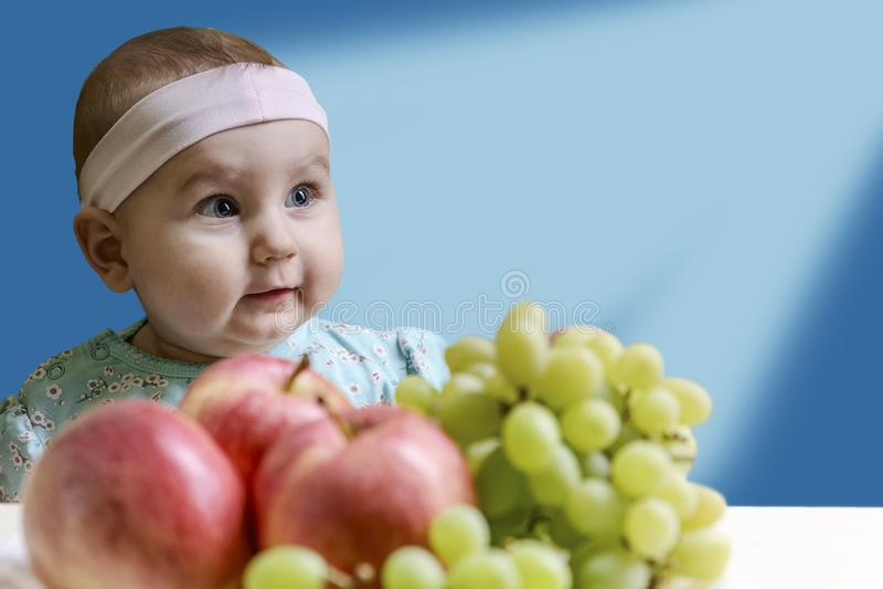 Enfant en bas âge positif devant une table avec le fruit frais sur un beau fond bleu photo stock