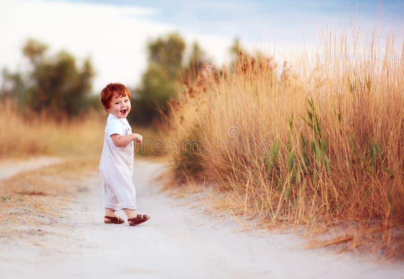 Enfant en bas âge roux mignon de bébé marchant le long du chemin d'été images stock