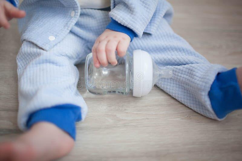 Enfant en bas âge s'asseyant à la table et au lait boisson photo libre de droits