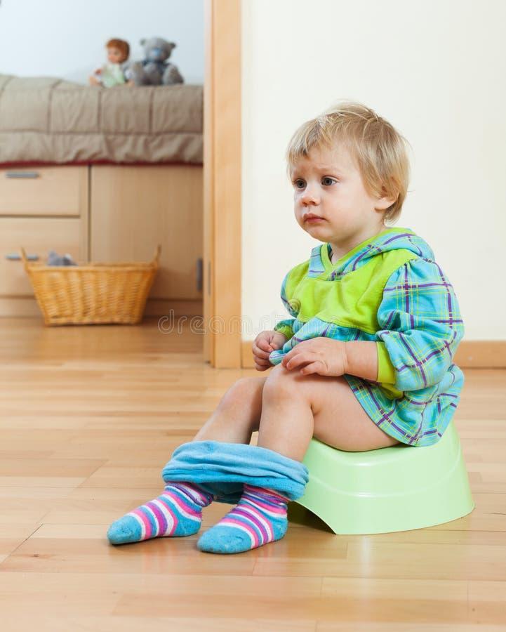 Enfant en bas âge s'asseyant sur le pot vert photo libre de droits