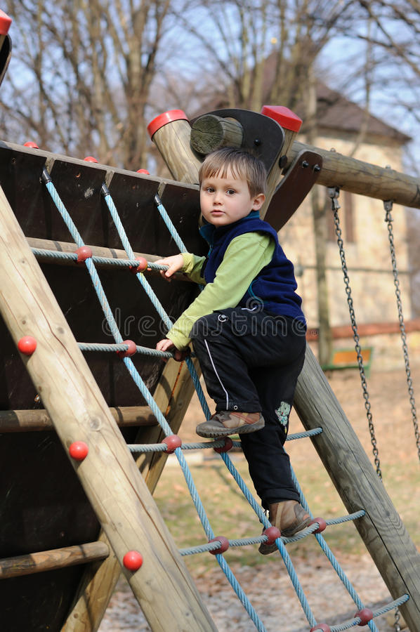 Enfant en bas âge sur l'échelle de corde images stock