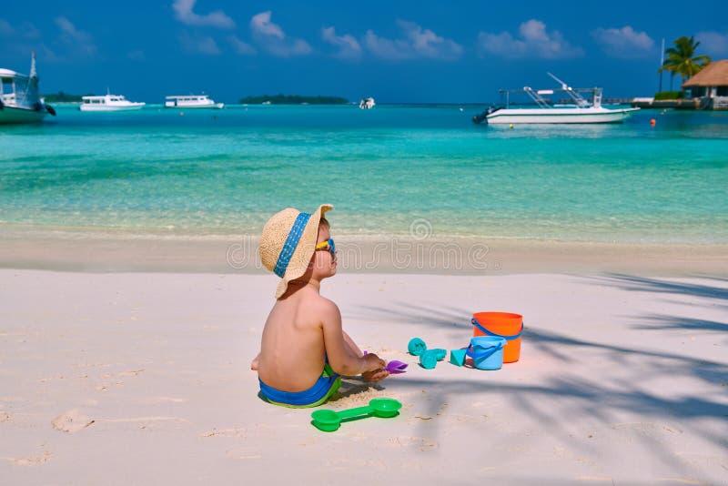 Enfant en bas ?ge trois an jouant sur la plage image libre de droits