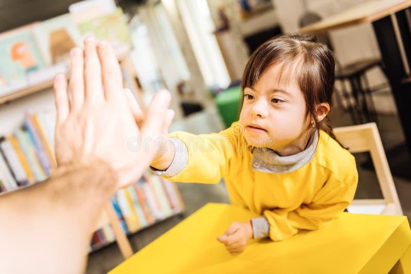 Enfant ensoleillé aux yeux noirs donnant haut cinq à son professeur image stock