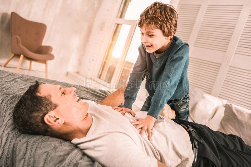 Enfant enthousiaste ambitieux racontant à son père attentif une plaisanterie futée image libre de droits