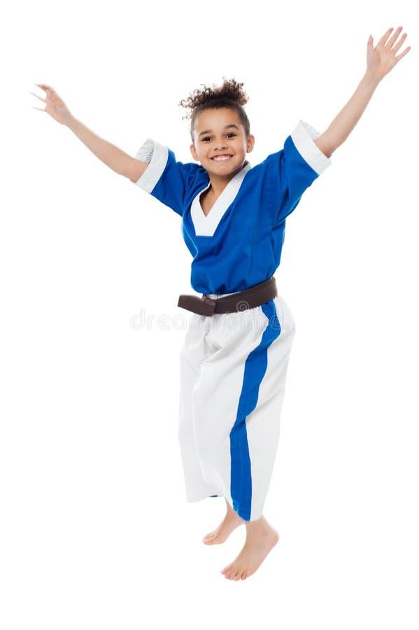 Enfant enthousiaste de jeune fille dans l'uniforme de karaté images stock