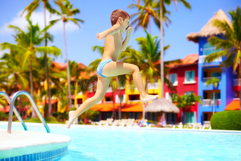 Enfant enthousiaste heureux sautant dans la piscine des vacances d'été images stock