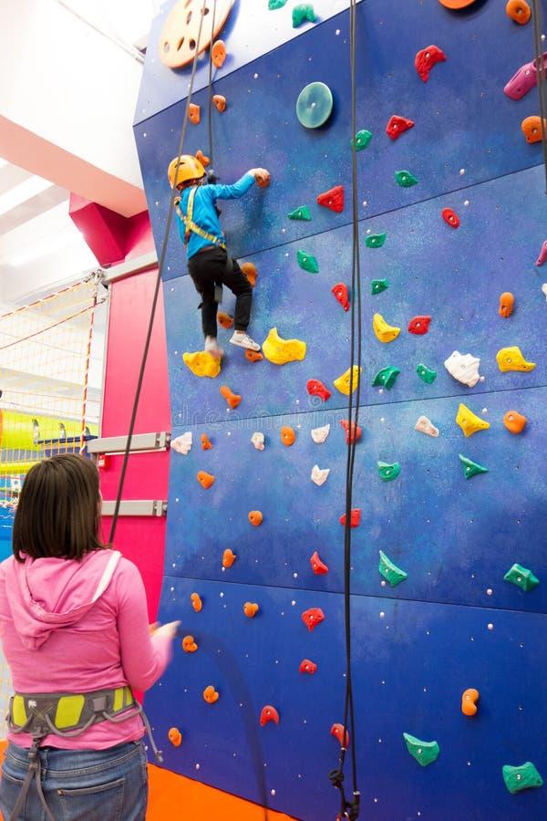 Enfant escaladant un mur d'intérieur photo stock