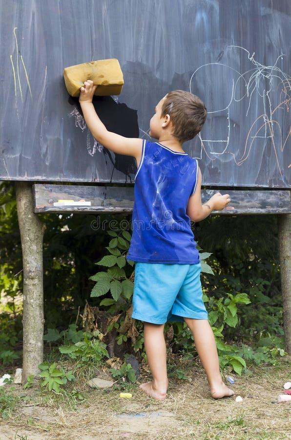 Enfant essuyant le tableau noir dans la salle de classe extérieure photos stock