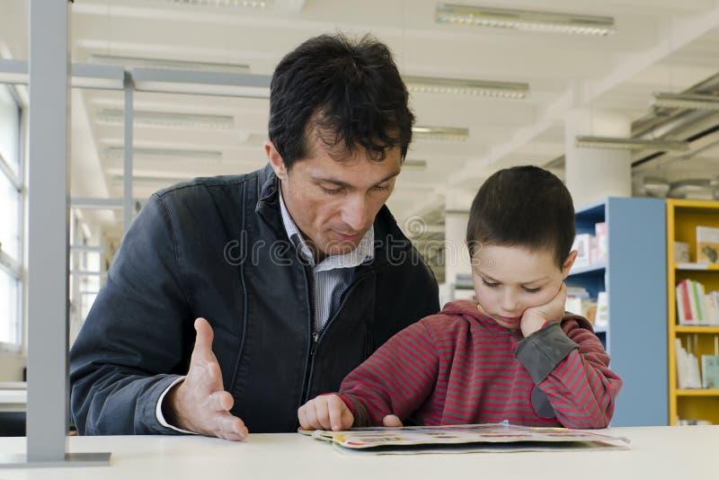 Enfant et adulte dans la bibliothèque photographie stock libre de droits