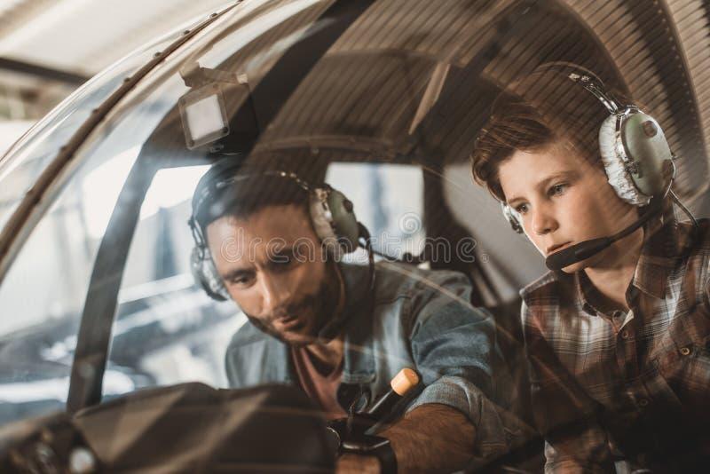 Enfant et homme focalisés dans l'hélicoptère photographie stock libre de droits