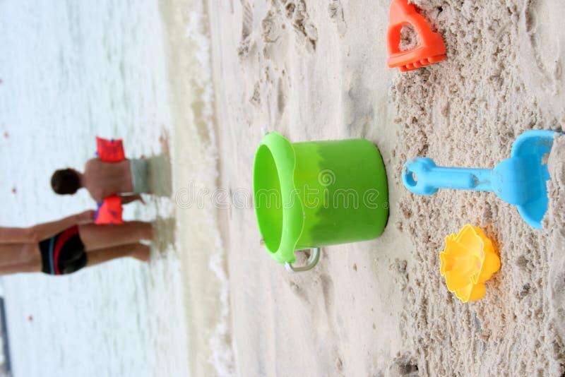 Enfant et jouets sur la plage photo stock