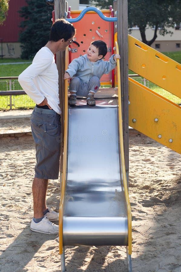 Enfant et père à la cour de jeu image stock