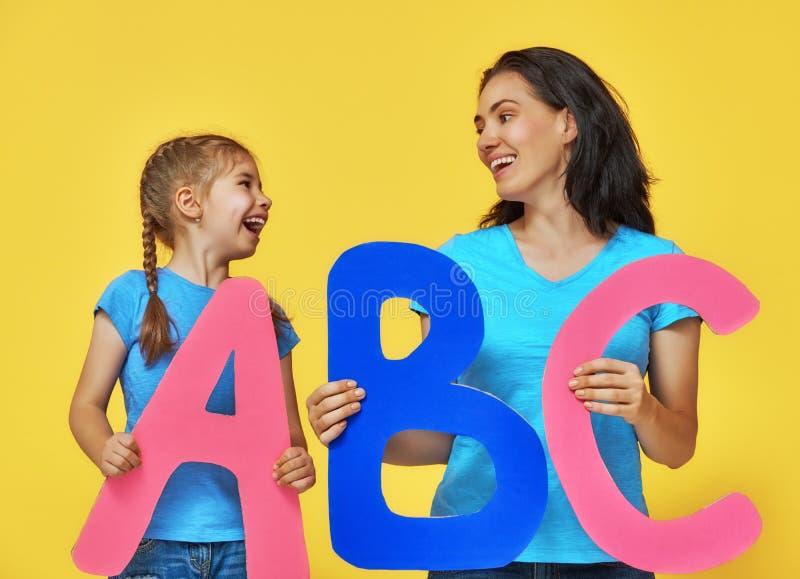 Enfant et professeur avec de grandes lettres photos stock