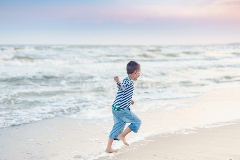 Enfant ex?cutant sur la plage Vacances d'?t? enfant heureux jouant sur la plage au temps de coucher du soleil photos stock