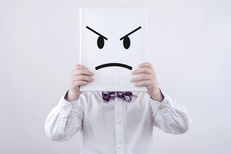 Enfant fâché avec le conseil blanc photographie stock