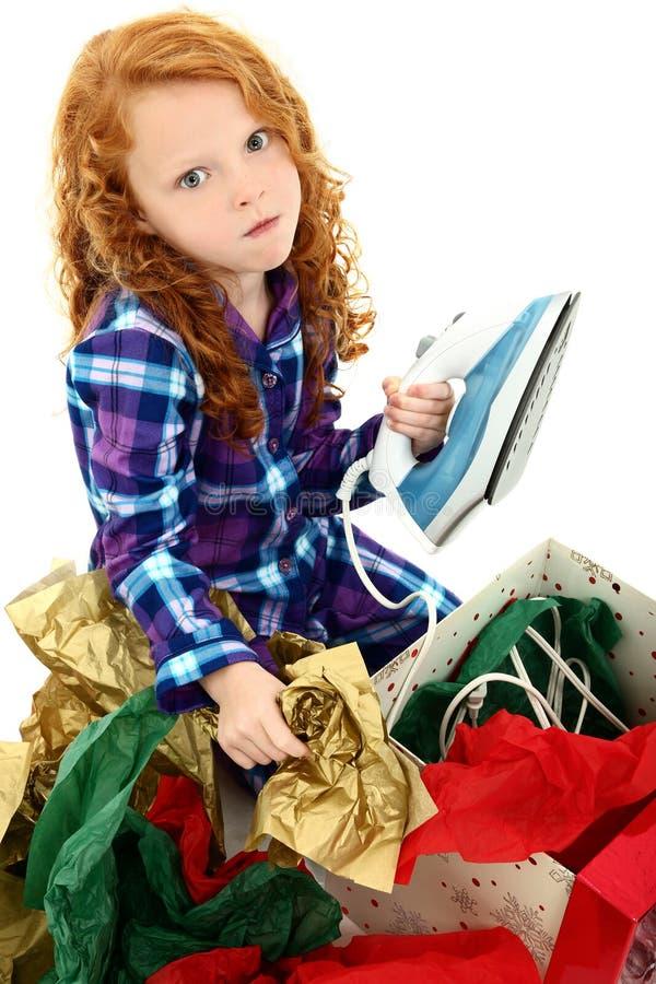 Enfant fâché de fille ouvrant un fer pour Noël image libre de droits