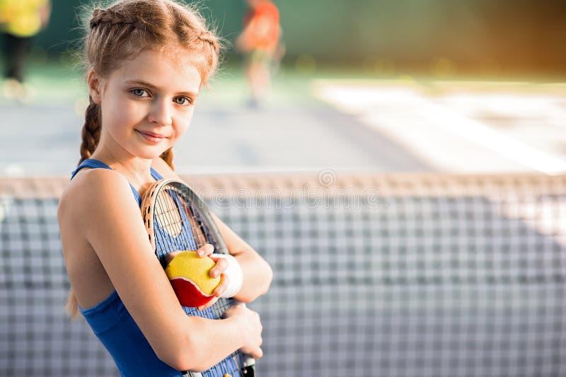 Enfant féminin gai jouant le tennis avec plaisir photographie stock libre de droits