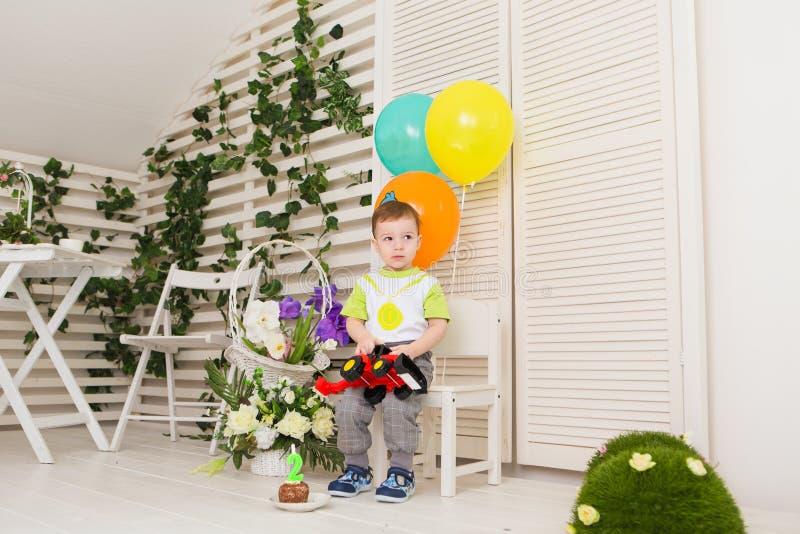 Enfant, fête d'anniversaire et concept d'enfance - petit garçon avec ballons et jouets à l'intérieur photos stock