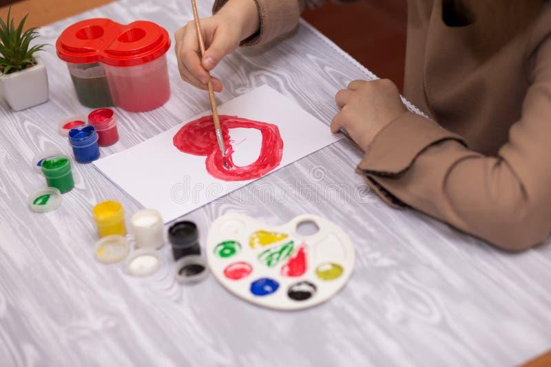 Enfant faisant la carte de voeux faite maison La petite fille peint le coeur sur la carte de voeux faite maison comme cadeau pour photographie stock libre de droits